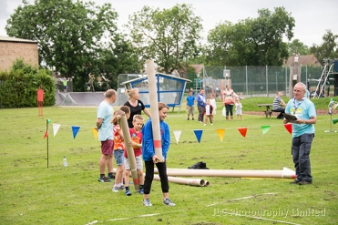 A queue of athletes line up to toss the caber.