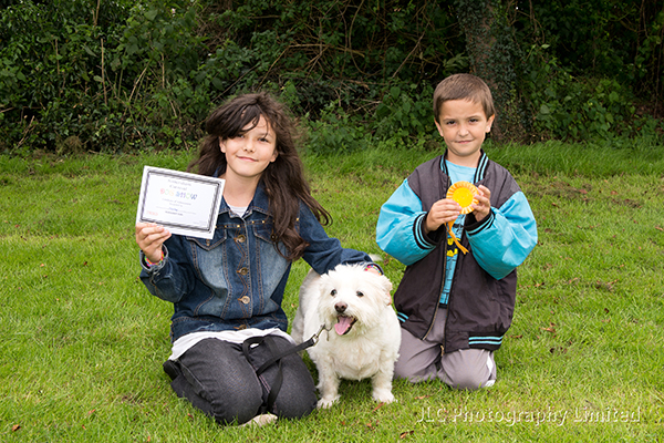 Two children with a rosette winning dog at the Somersham Carnival Novelty Dog Show 2014.