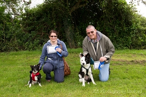 Two adults with two rosette-winning dogs at Somersham Novelty Dog Show 2014.