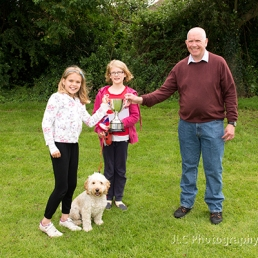 Two girls and their dog, awarded trophy at Somersham Carnival Dog Show by Neville Diss, compare.